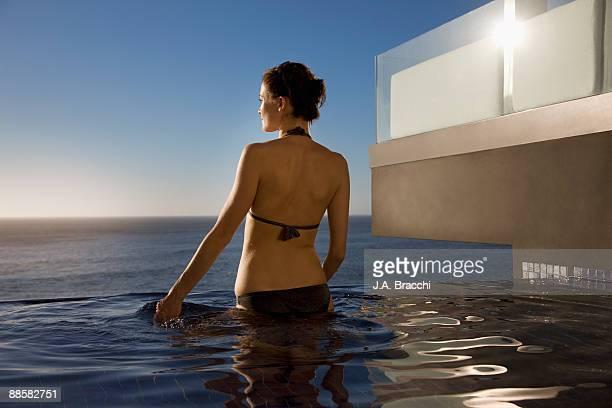 Woman wading in infinity pool near ocean
