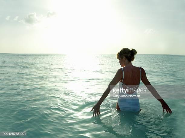 Woman wading in ocean, rear view