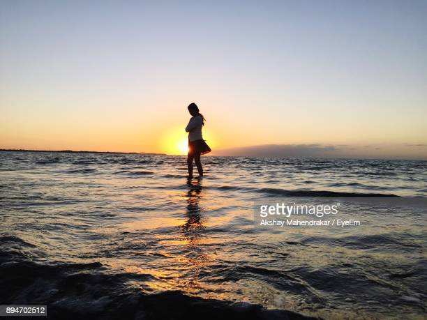 Woman Wading In Sea Against Clear Sky
