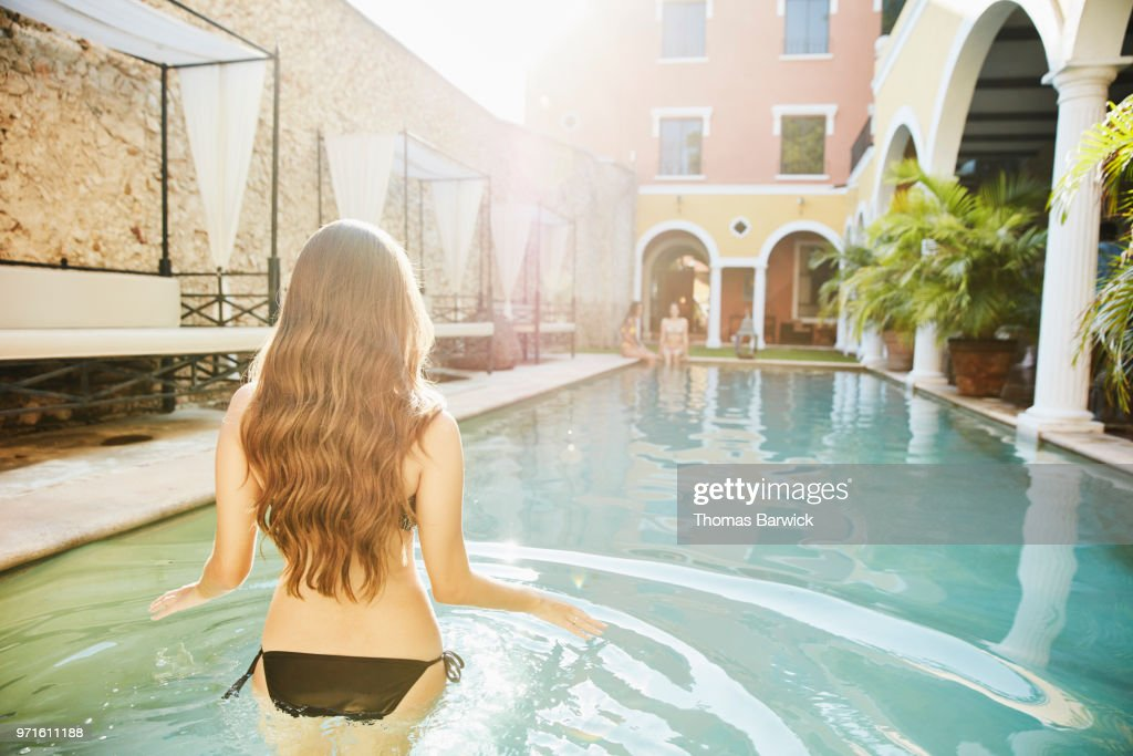 Woman wading into pool in courtyard of hotel while friends sit on edge : Stock Photo