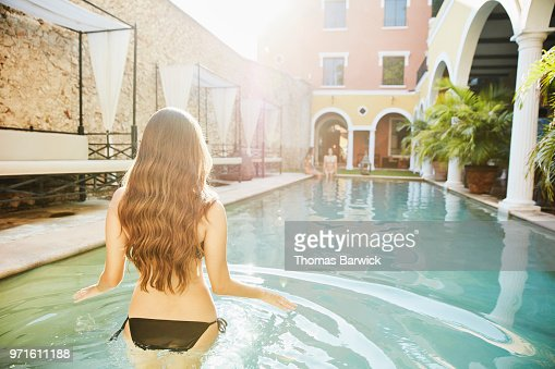 Woman wading into pool in courtyard of hotel while friends sit on edge