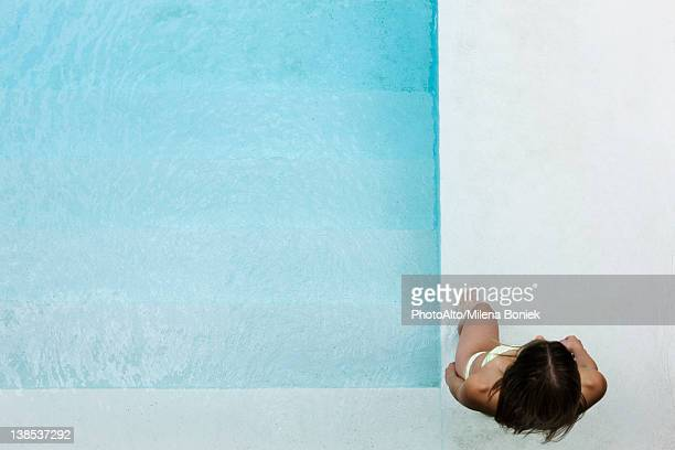 Woman wading into pool