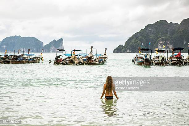 a woman wading into the ocean. - femme blonde en maillot de bain vue de dos photos et images de collection