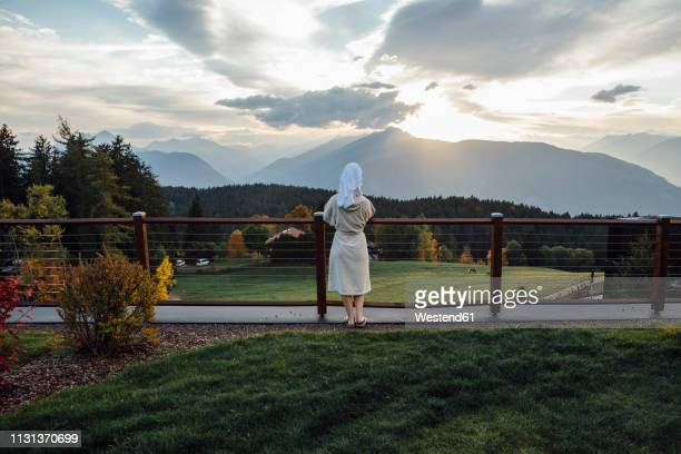 woman waering bathrobe and turban standing at a fence looking at landscape - bathrobe stock pictures, royalty-free photos & images