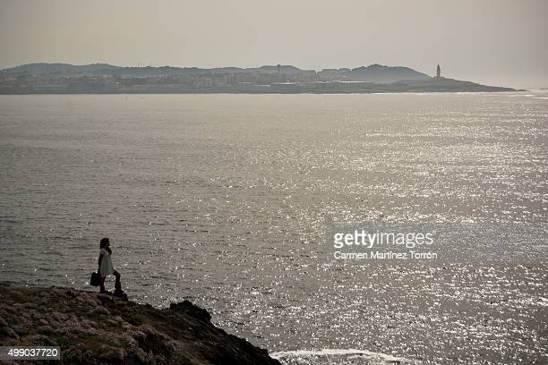 woman waiting alone with suitcase on a cliff, a coruna. spain - carmen bella foto e immagini stock