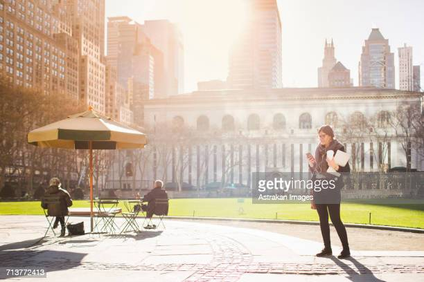 woman waiting at bryant park against new york public library on sunny day - bryant park stock pictures, royalty-free photos & images