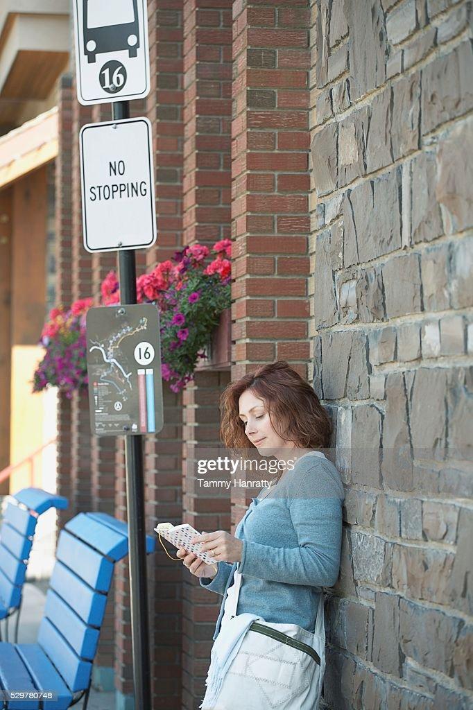 Woman waiting at bus stop : Bildbanksbilder