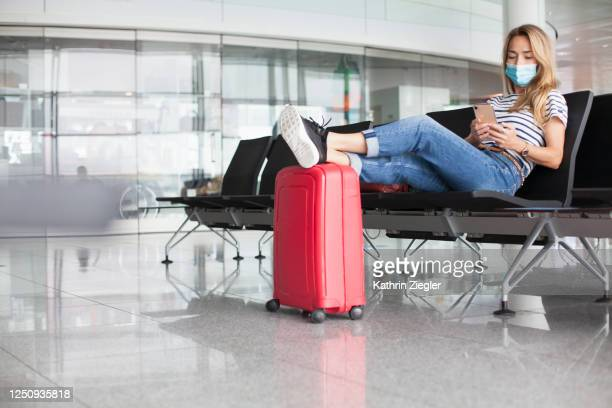 woman waiting at empty departure gate, wearing protective face mask - travel stock pictures, royalty-free photos & images