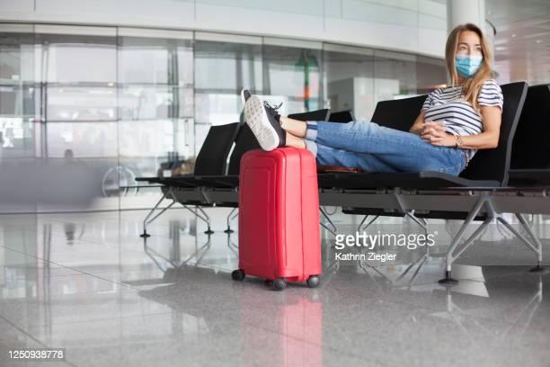 woman waiting at empty departure gate, wearing protective face mask - passagier stock-fotos und bilder