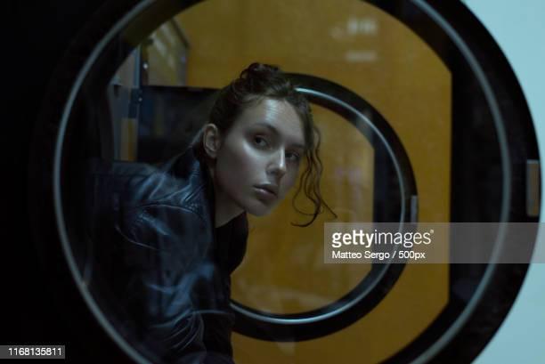 woman waiting at laundromat - waschsalon stock-fotos und bilder