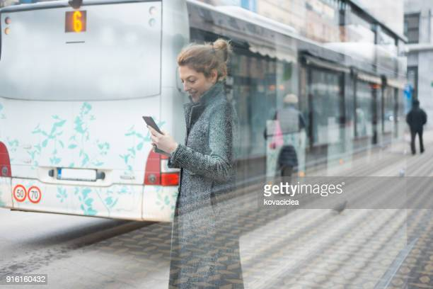 woman waiting at the bus station and using smart phone - social awareness symbol stock photos and pictures