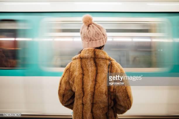 frau wartet an der u-bahnstation in paris - bahnhof fotos stock-fotos und bilder