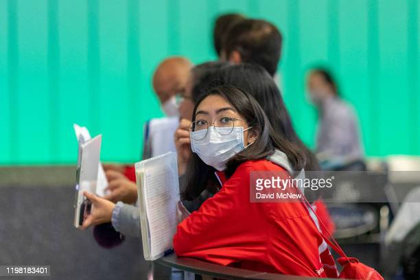 A woman waiting for an international traveler to arrive to LAX Tom Bradley International Terminal wears a medical mask for protection against the...
