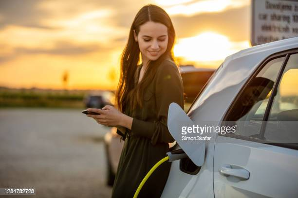 woman waiting for electric car to charge in the parking lot at sunset - hybrid car stock pictures, royalty-free photos & images