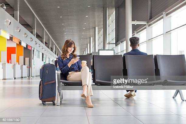 woman waiting for flight at the airport lounge - geschäftsreise stock-fotos und bilder