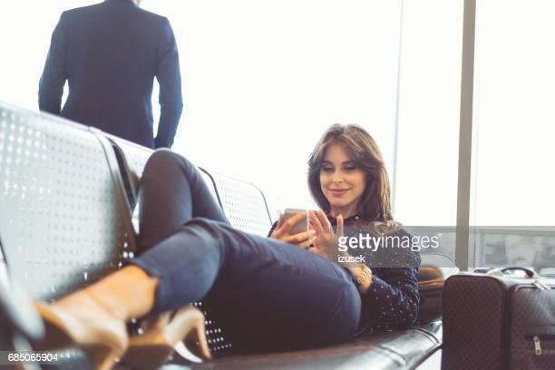 Frau warten auf ihren Flug am Flughafen-lounge