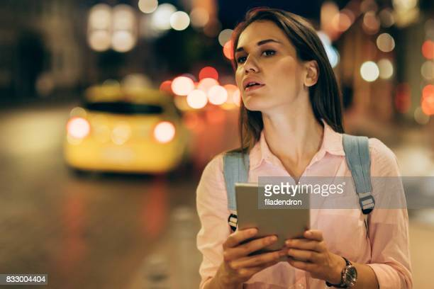 Woman waiting for her taxi on the street