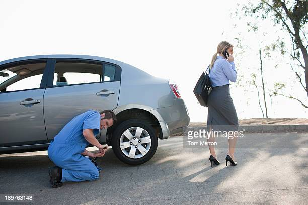 Woman waiting for mechanic to change car tire