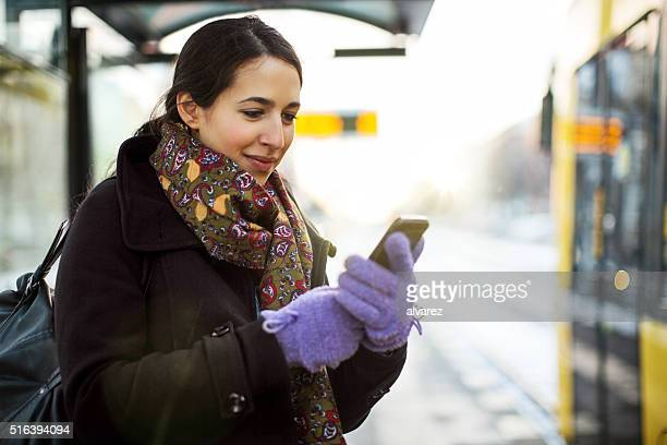 Woman waiting for subway train using mobile phone