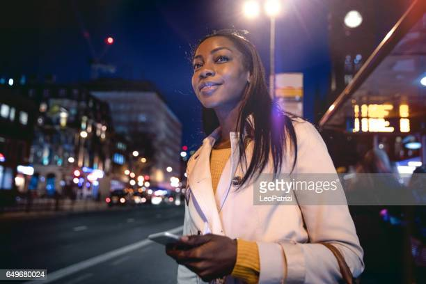 woman waiting for the bus in london - car pooling stock photos and pictures