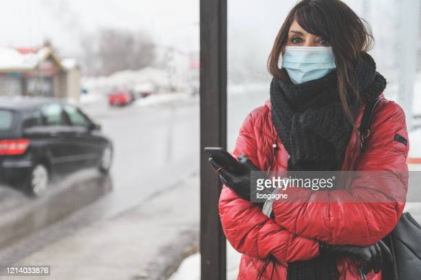 woman waiting for the bus - coronavirus winter stock pictures, royalty-free photos & images