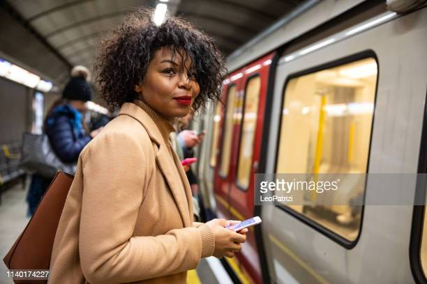 woman waiting for the subway train - london underground stock pictures, royalty-free photos & images