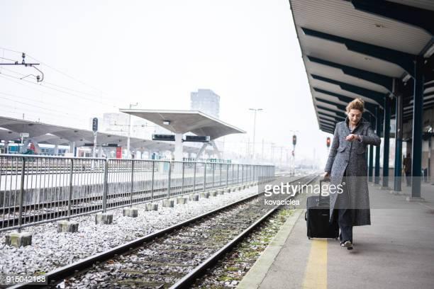 Frau auf den Zug warten und überprüfen der Zeit