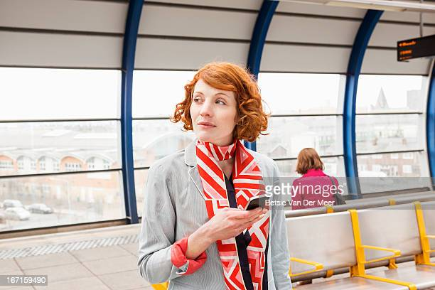 Woman waiting for train on platform.