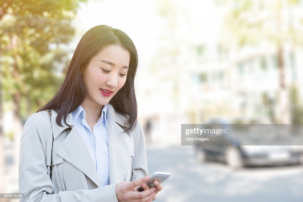 Woman waiting for Uber in the street : Stock Photo