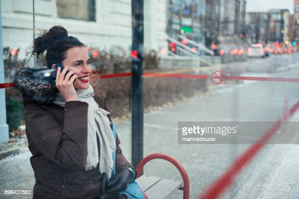 """woman waiting in bus stop cummuting in winter. - """"martine doucet"""" or martinedoucet stock pictures, royalty-free photos & images"""