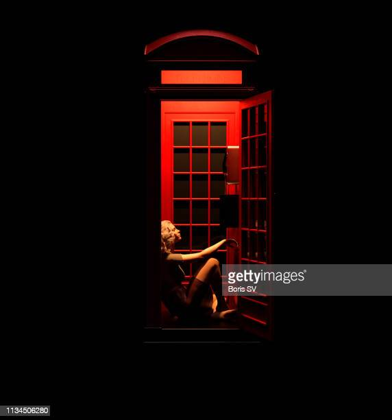 Woman waiting in red phone booth