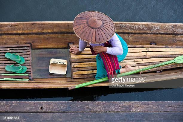 Woman waiting on her pirogue under rain