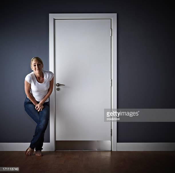 woman waiting outside ladies toilet - wachten stockfoto's en -beelden