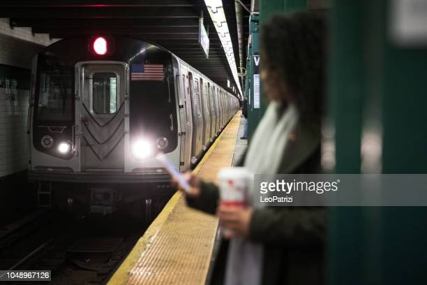 woman waiting the subway train - new york city subway stock pictures, royalty-free photos & images