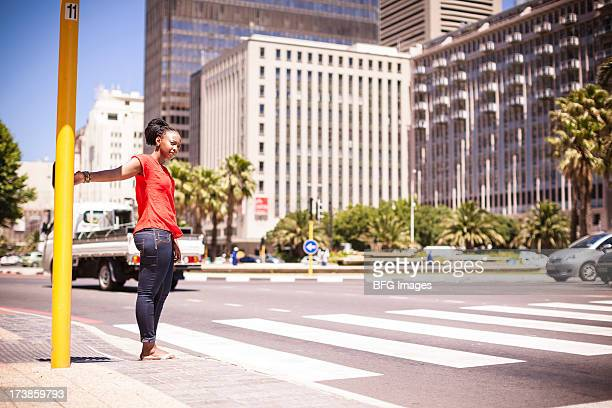 Woman waiting to cross a busy road, Cape Town, South Africa
