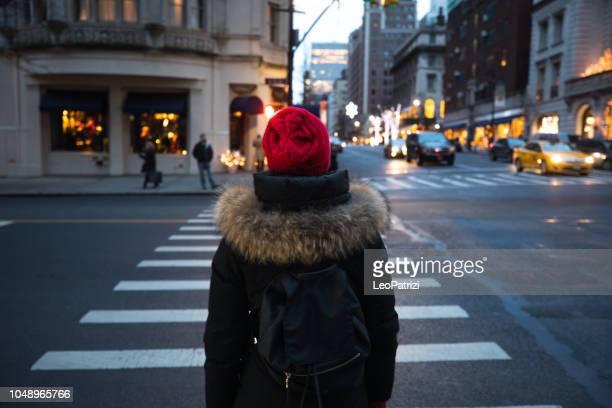 mujer esperando para cruzar la calle en el centro de manhattan - nueva york - cruzar fotografías e imágenes de stock