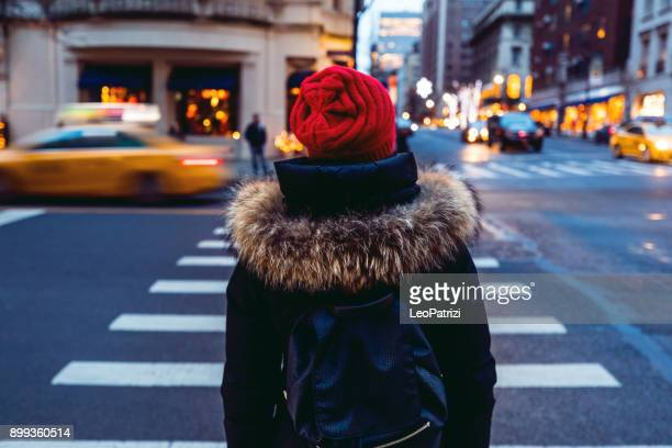 woman waiting to cross the street in downtown manhattan - new york city - pedestrian crossing stock photos and pictures
