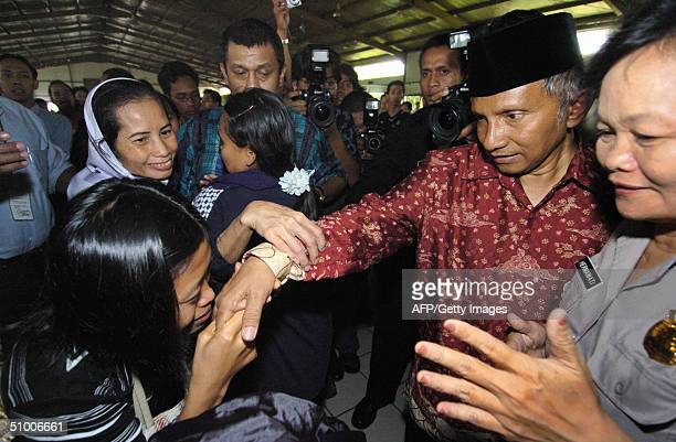 A woman waiting to depart kisses the hand of Indonesian presidential candidate Amien Rais as he visits an immigration center at one of Jakarta's...