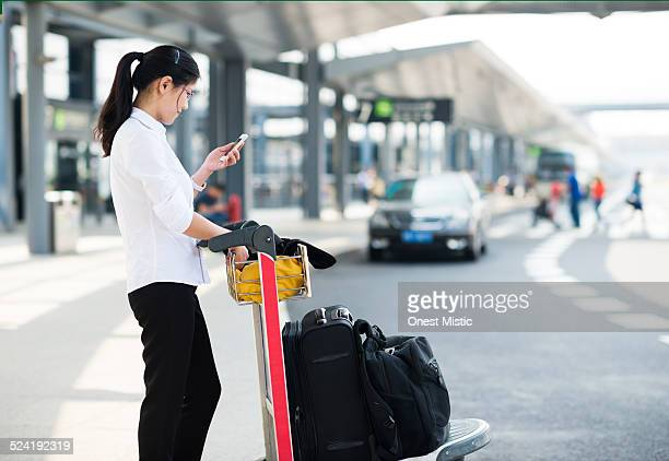 Woman waiting with luggage at airport