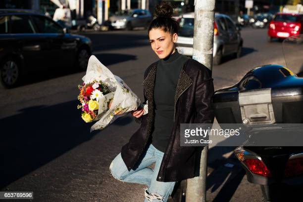 Woman waitingwith a bunch of flowers in her hand