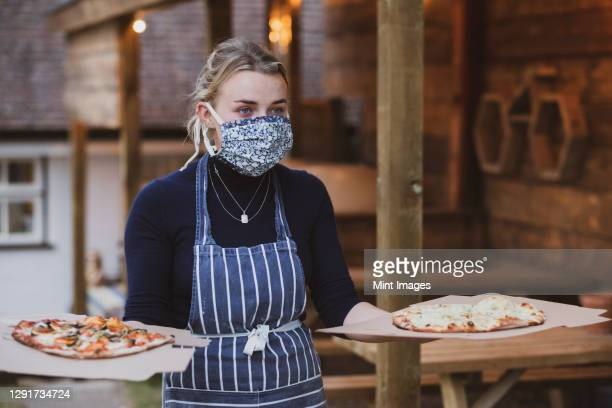 woman waitress in apron and face mask holding plate of pizza. - epidemic stock pictures, royalty-free photos & images