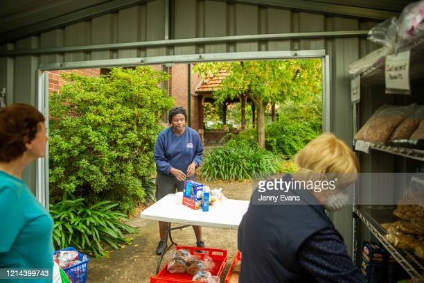 A woman waits as volunteers Margaret Baseley and Kerin Brown pick food items at St Paul's Anglican Church in Burwood on March 24 2020 in Sydney...