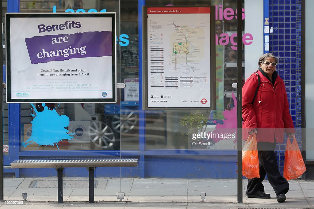 A woman waits at a bus stop in North London near a poster informing of changes to the benefits and tax system that came into force yesterday, on April 2, 2013 in London, England. The widespread changes include a cut in housing benefit payments for working-age social housing tenants whose property is deemed larger than they need and council tax support payments being administered locally.