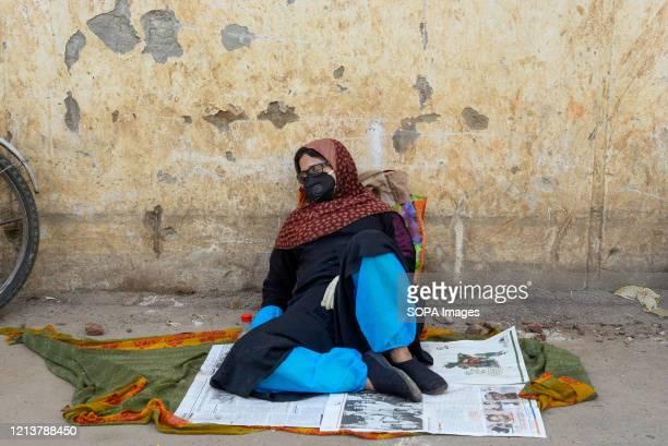 Woman waits at a hospital for COVID-19 swab tests during the coronavirus crisis. Bangabandhu Sheikh Mujib Medical University is being used to conduct...