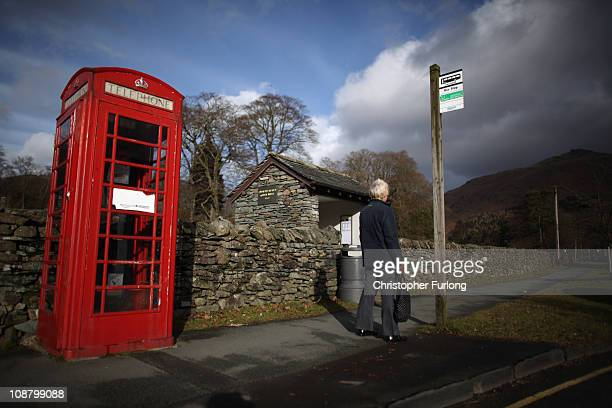 A woman waits at a rural bus stop iun Grasmere in the Lake District countryside on February 3 2011 in Grasmere England More than two thirds of...