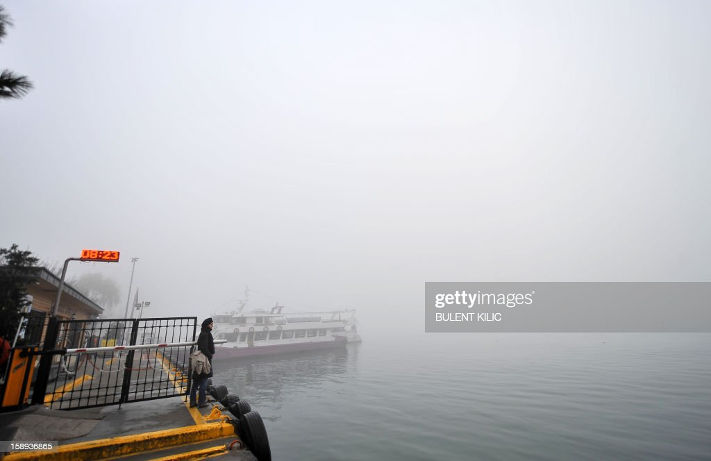 A woman waits at Kabatas landing early on January 4, 2013, in Istanbul, after heavy fog restricted boat traffic on the Bosphorus.