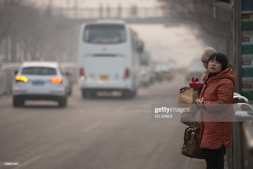 A woman waits for a bus beside a busy road in Beijing on January 22, 2013. Beijing has the worst traffic jams in the world, as record traffic levels take their toll on people's health, productivity and social lives, a study by IBM reported early January. Beijing and Mexico City scored 99 out of 100 in IBM's commuter pain index, followed by Johannesburg, Moscow and New Delhi. AFP PHOTO / Ed Jones