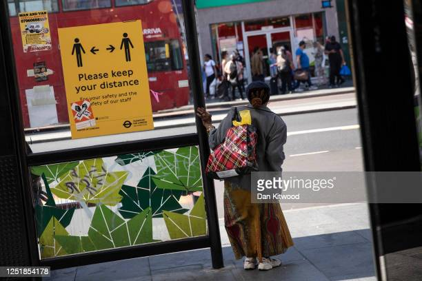 A woman waits for a bus next to a social distancing sign in Brixton on June 24 2020 in London England Yesterday the Prime Minister Boris Johnson...