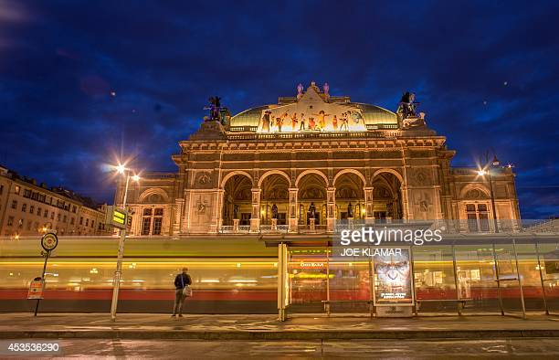 A woman waits for a city tram in front of litup Wiener Staatsoper Vienna's State Opera building during the twilight in the city center of Vienna on...