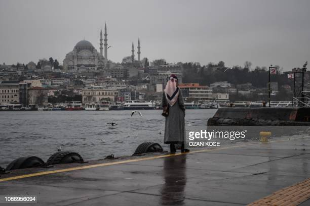A woman waits for a ferry boat next to the Bosphorus Strait across from the Suleymaniye mosque on January 23 2019 in Istanbul